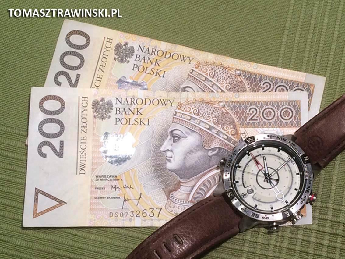 dwa banknoty dwustuzłotowe i leżący na nich zegarek