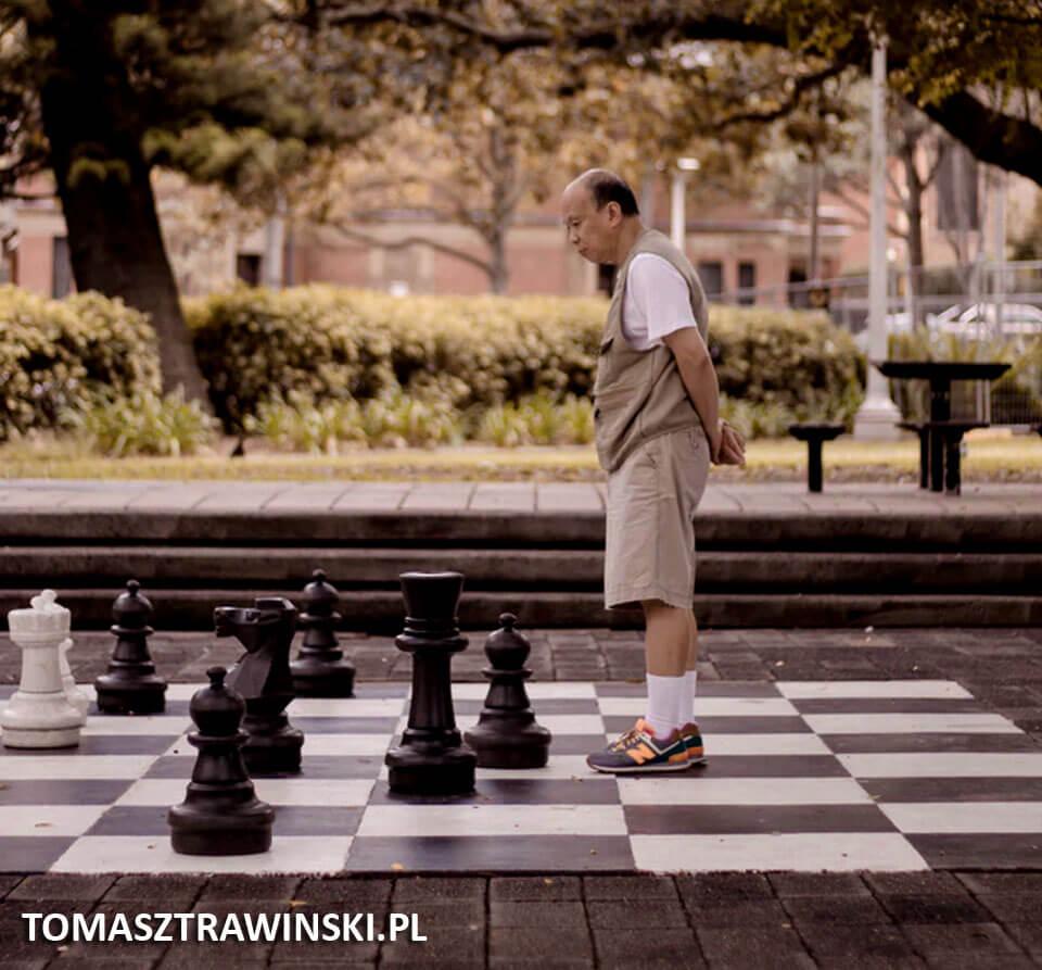 Mężczyzna stoi nad dużymi szachami rozstawionymi na ziemi